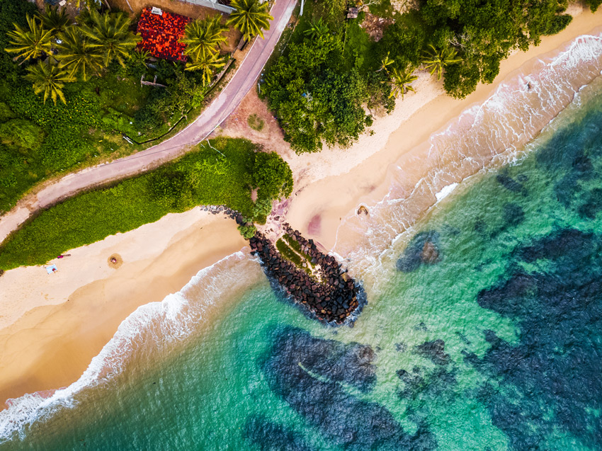 SRI-LANKA-BEACH-Aerial-view-of-the-tropical-beach-with-palm-trees-on-the-shore-and-coral-reef-in-the-sea.-Sri-Lanka