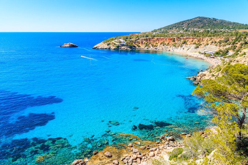 ibiza-beaches-Cala-d'Hort-bay-with-beautiful-azure-blue-sea-water,-Ibiza-island,-Spain